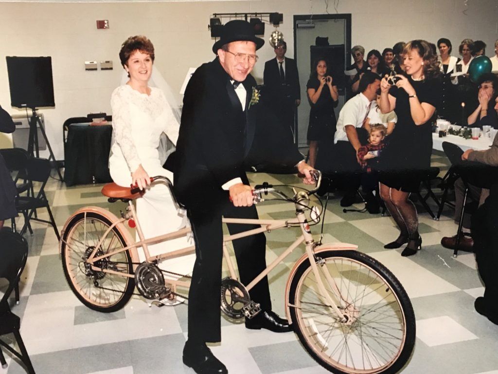 Lisa Sweitzer and husband on wedding day with two seater bike